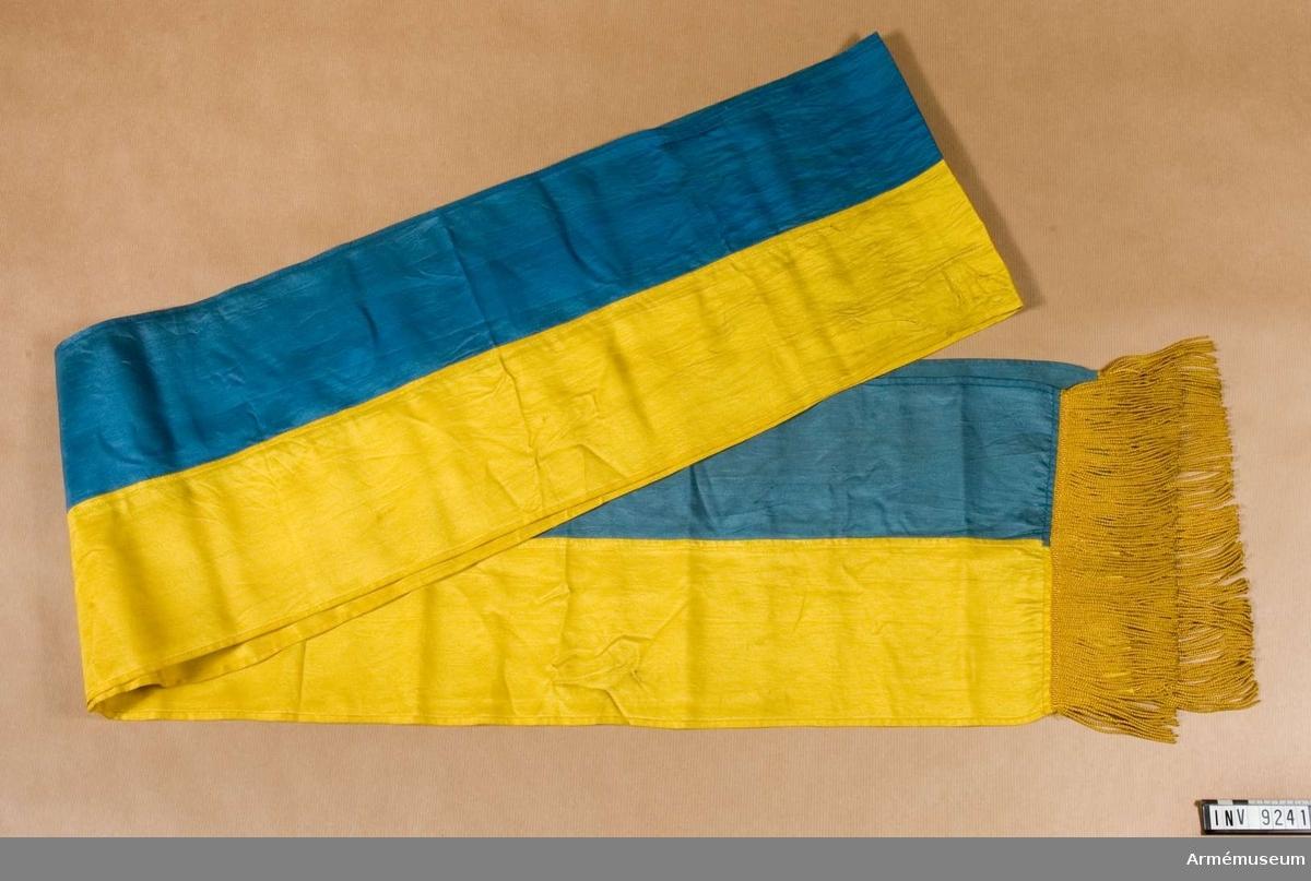 """Sydd för hand i hälften blått och hälften gult och blått siden. Kortsidorna försedda med en gul silkefrans. Fransen är enkel och utförd i s k """"drejat"""" natursilke. Sidenet är nött och trasigt särskilt i det gula sidenet där fanbandet har knutits runt stången."""