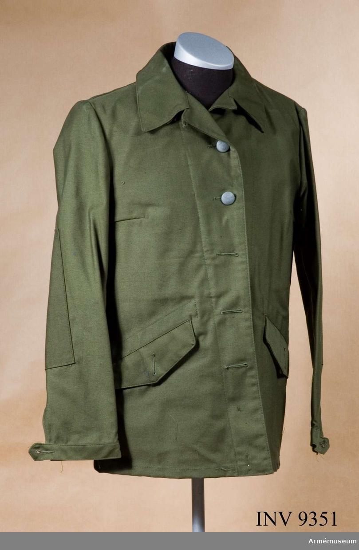 Storlek C 40. Tillverkad av olivgrön varpsatin. Fram till 1973 tillverkades varpsatinen i 100 % bomull. Man övergick då efter försök med olika fibersammansättningar till en blandning av 50 % polyester och 50 % kammad bomull. Därigenom erhölls en kvalité med större såväl slitstyrka som tvätthärdighet. Jackan är enradig, knäppt med fem stora uniformsknappar m/1939, högknäppt i halsen där den knäpps med en polyamidknapp på en knapphålsslejf. För underknäppning är två polyamidknappar anbringade nedtill på högra insidan och finns motsvarande knapphål på vänster sida. Två insydda sidfickor med  spetsfasonerade ficklock knäppta med stor uniformsknapp m/1939. Förstärkningar på undersömmarna. För att reglera ärmvidden är ärmarna nedtill försedda med slejf och två polyamidknappar på varje ärm. Halvt livfoder av gråbrungrön fodertwills med en på höger sida påstickad innerficka med ficklock knäppt med polyamidknapp. Ovanför innerfickan en pennficka. Som tjänstetecken anlägges kragspegel m/1958 med invävt försvarsgrentecken - för armén, armétecken - på bägge kragsnibbarna av ej förordnad personal. Förordnad personal anlägger försvarsgrenstecken på höger kragsnibb och tjänsteklass (tjänstegrupp) på vänster kragsnibb. Märkning: På insidan under hängaren vävd storleksetikett: C 40. Nedanför och till höger stämpel:Tre kronor 1977 OLJON (firmanamnet för tillverkaren Olsson & Johansson, Malung).