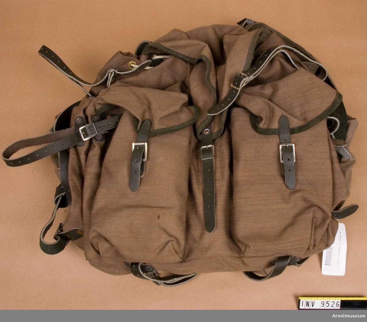 Består av tre mindre väskor och ryggsäck. Midjebältet är  av läder och cordband. Finskt material. Gåva från FMV i Solna.