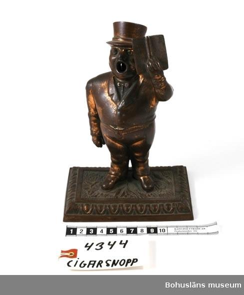 Ur handskrivna katalogen 1957-1958: Cigarrsnoppare H: 19 cm. Kopparstatyett i form av en sångare m. öppen mun. Då man trycker ner armen, passerar en kniv i sångarens mun. Hel.  Lappkatalog: 95