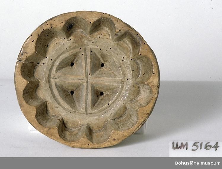 Rund ostform skuren ur ett trästycke. I mitten ett nedsänkt, utskuret solhjul/kors med fyra avrinningshål i botten. Ovanför löper tolv halvrunda snitt längs kanten. Sprucken  kant. Skadedjursangrepp.  Ur handskrivna katalogen 1957-1958: Liten ostform D: c:a 18 cm; H. c:a 5 cm; skuren ur ett enda trästycke, 4 genomg. hål. Sprucken, maskäten.