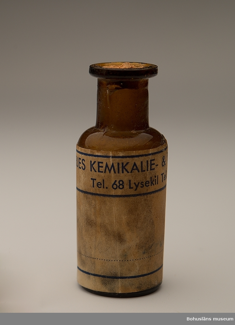 """Liten flaska i brunt glas med kort som delvis har brutis av.  Etikett: """"Börjes kemikalie & färgaffär. Tel. 68 Lysekil."""" En handskriven text har presenterat innehållet. Tyvärr oläsligt."""