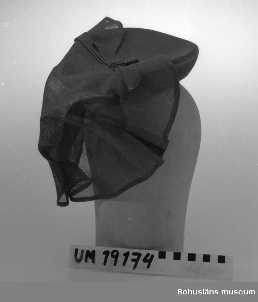 471 Tillverkningstid 1940-TAL 394 Landskap BOHUSLÄN  Liten vinröd hatt i glesvävt tyg med löst tygstycke fastsatt bak med rosett och nackband.    Se UM19130.