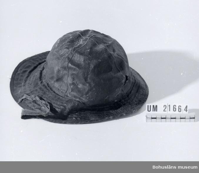 Föremålet visas i basutställningen Kustland,  Bohusläns museum, Uddevalla. 594 Landskap BOHUSLÄN  Hatt med kulle ihop sydd av fyra trekantiga bitar. Brätte som är större bak i nacken än framtill. Foder med öronlappar och ett band att fästa under hakan med en knapp. Hatten är svart på utsidan och fodret brunt. Brättet är större baktill som hinder för regn att rinna in vid nacken. Den är sliten och har ett hål framtill i kullen.  Inventerad 1996-10-09 GH.  UMFF 40:6