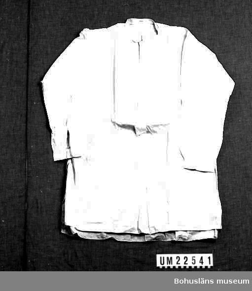 """410 Mått/Vikt ! ÄL 53 CM 594 Landskap BOHUSLÄN  Vit skjorta med stärkt bröst utan löskrage, på insidan vid kragenmärkt med svart bläck eller tusch: """"1536"""" och i svart tryck: """"25 H 40 34307"""". Samt vid nacken påsydd lapp av tyg med text i rött: """"Daniel Mattsson & Co Herrekipering Uddevalla"""".  UMFF 125:8"""