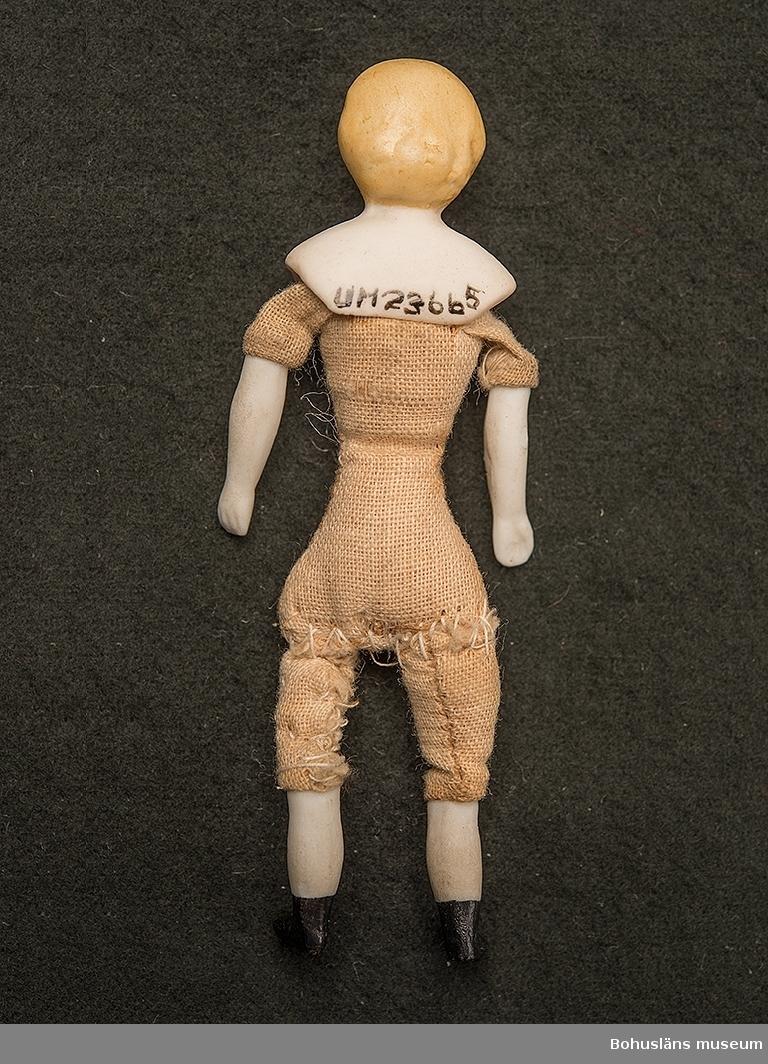Docka med tygkropp och med nederben, nederarmar och huvud av biskviporslin. Huvudet bemålat.  Dockans kropp är hemtillverkad.