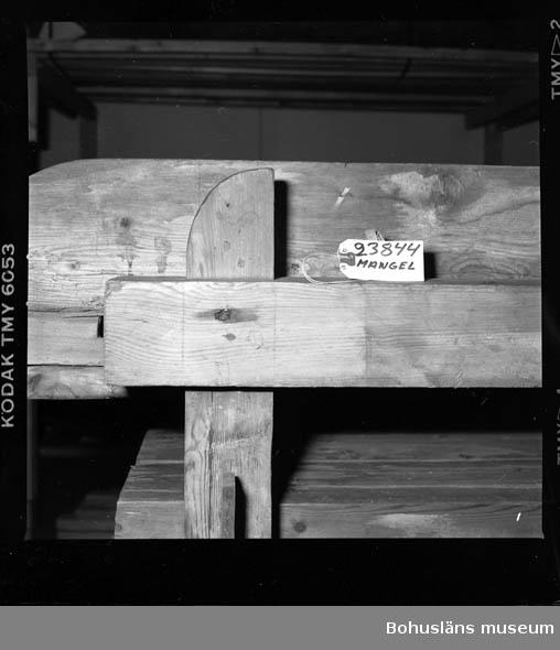 Trämangel med vagga för stenen. Två tjockare, två tunnare. Beata Olsson  öppnade första lanthandeln i området vid Brattås, Morlanda (Henån) på 1880-talet i hus vid vägen. Mangeln uthyrdes samtidigt som lanthandeln drevs. Den var placerad i ett magasin bredvid och hyrdes av byns (Brattås) invånare. Under senare år användes den mest av Beata Olssons släktingar. Nedmonterades något år innan den skänktes till museet. Beata Olsson kom från Tegneby  socken. Givaren lanthandlare i Brattås. Nuvarande affären flyttad snett över vägen längre ned i backen.