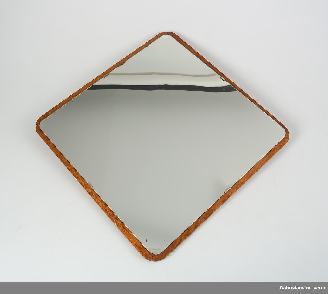 Kvadratiskt spegelglas något asymmetriskt påsatt, betsad träram av fur. Rundade hörn. Upphängd i ena hörnet.  Föremål från Brorssons Damfrisering i Kungshamn, se UM023941.