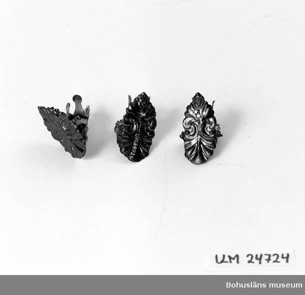Formen är akantusliknande. Blå metallglänsande yta. Låg i kexburk UM024720 när de inkom till museet.