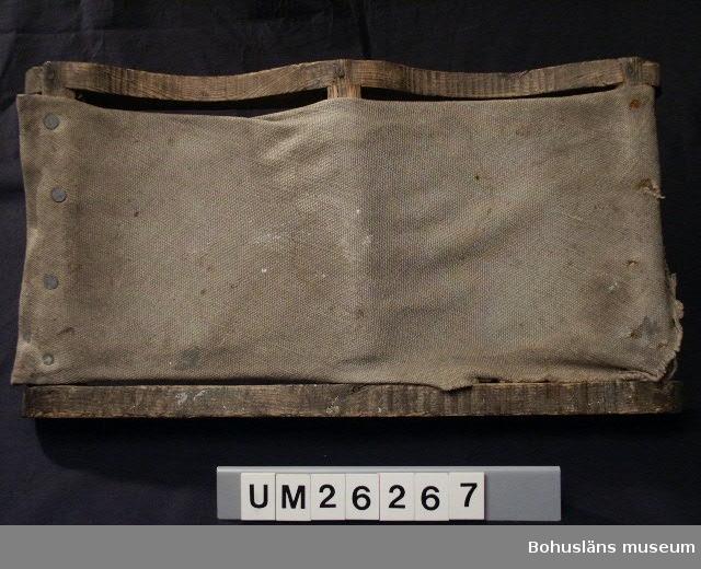 Föremålet visas i basutställningen Kustland, Bohusläns museum, Uddevalla.  Två parallella träskivor varav den ena utsågad med en våglinje. Sammankopplade med tre  trästavar, en i mitten och en i vardera kant. Över dessa fastnitat säckväv .  Använd som knäskydd vid arbeten i knästående ställning, t ex vid golvskurande.  Personuppgifter om ägaren se UM 26259.