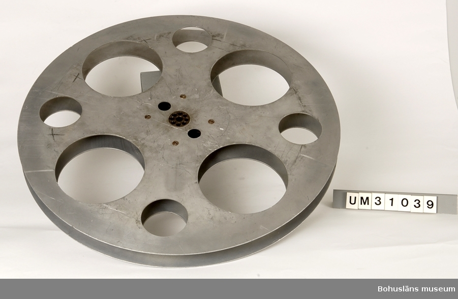 Filmspole, använd tiill filmprojektor UM31031.  Placerad i trälår UM31034.  Projektorn är tillverkad av AEG på 1920-talet och har använts i Folkets Hus i Sjöbol vid Lysekil.  Till projektorn hör en lång rad delar och olika tillbehör, UM31031 - UM31062.  För ytterligare upplysningar om filmprojektorn, dess olika delar och användning, se UM31031.