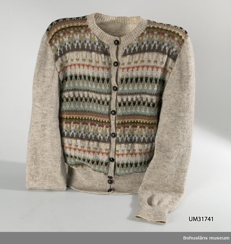 """Stickad kofta med långa ärmar i mönstret Härskogen, komponerat av Anna-Lisa Mannheimer Lunn före 1947. Slätstickad i gråmelerat ryagarn (kallat finskull) och färginslag i finull och eja-garn. Mönstrade framstycken, enfärgat bakstycke och ärmar.  Mönster i slät- och avigstickning i 11 olika nyanser av ljusblått, gult, grått,  brunt, vitt, grönt och rött. Bred ribbstickning i midjelinningen, ribbstickade ärmmuddar och ribbstickad halskant.  Sju bruna och en svart plastknapp, ej original. Vid gåvotilfället satt en säkerhetsnål fästad i knappslån med 6 gjutna lättmetallknappar med präglat mönster föreställande Bohus fästning. Givaren kallade knapparna """"Bohusknappar"""". Dessa har dock aldrig använts av företaget Bohus Stickning. Koftan saknar Bohus Sticknings etikett i nacken.  Jämför UM027877 Mönsterritning, UM016385 Fingervante, UM027464 Vante, UM031442 Mössa, UM031443 Halsduk, alla i mönstert Härskogen."""