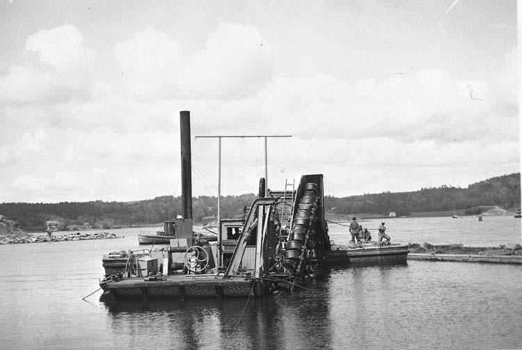 """Enl. tidigare noteringar: """"Uddevalla stads mudderverk i arbete 1936, för småbåtshamn vid Skeppsviken. Repro 1986 av foto 6x9""""."""