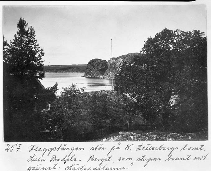 """Text på kortet: """"257. Flaggstången står på W. Zetterbergs tomt. Lilla Bodele. Berget som stupar brant mot vattnet: """"Hästepallarna""""."""