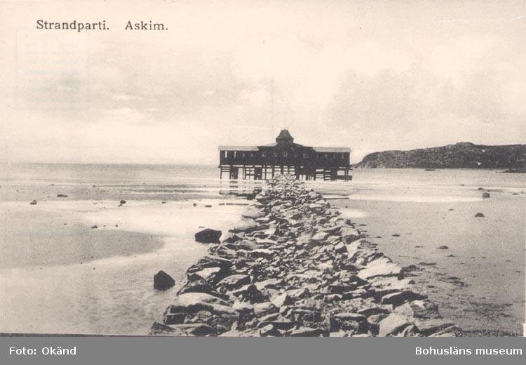 "Tryckt text på kortet: ""Strandparti. Askim""."