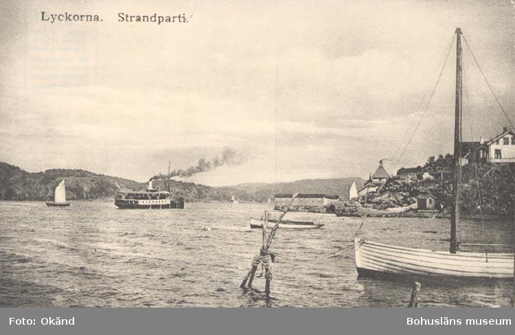 """Tryckt text på kortet: """"Strandparti. Lyckorna"""". ::"""
