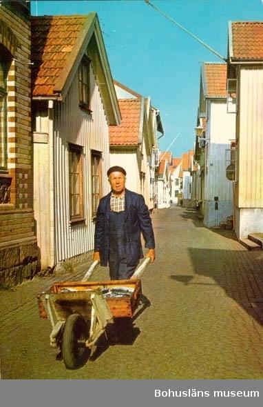 """Tryckt text på kortet: """"Lysekil: """"Kornöbon"""" Robert Arvidsson ropar ut färsk makrill på Gamla Strandgatan."""" """"Clara-Förlaget, Lysekil. tel. 10919,10320."""""""