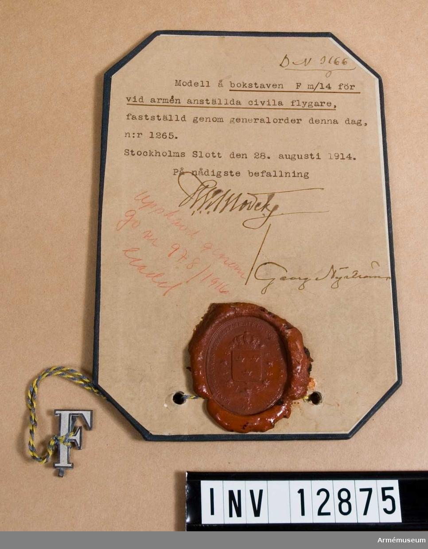 Grupp C I. Modell på bokstaven F m/1914 för vid armén anställda civila flygare, fastställda genom go nr 1265 den 28. augusti 1914. Deposition från Arméförvaltningens intendenturdepartement, modellkammaren.