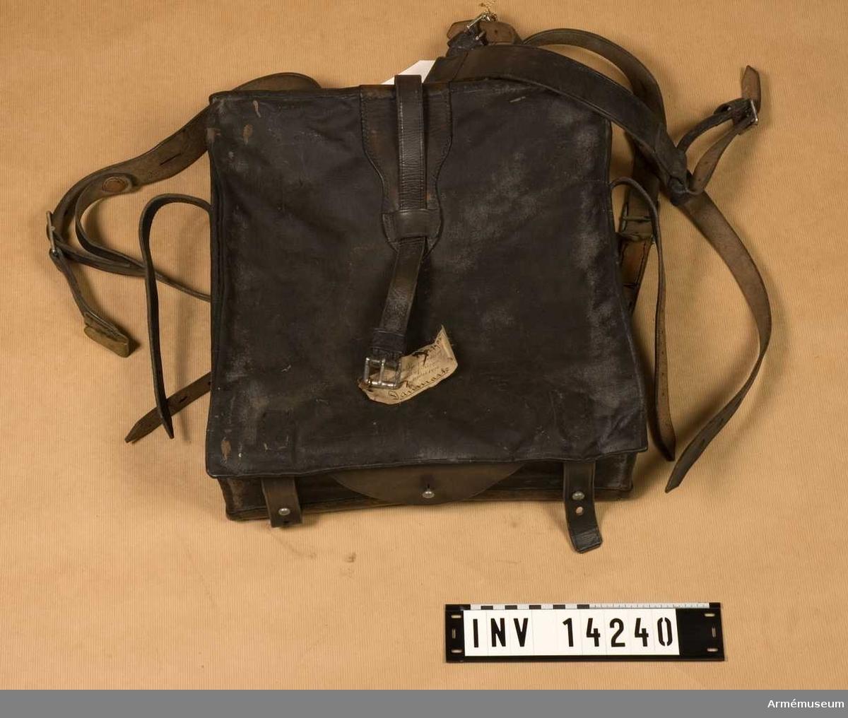 """Grupp C II. Ränsel. Danmark 1914. Ränseln (brödväskan) tillverkad av svart linne (31 cm lång och 26 cm bred) med lock som stänges med två svarta knappar fastsydda vid väskan. Väskan har två stämplar """"1913"""" och """"PRM"""" - prövemaessigt (modellenligt). Väskan har en innerpåse av grov linnelärft med fickor och samma stämplar. Axelgehäng av svart läder, 2,5 cm brett, med spänne av vitmetall. """"PRM"""" och """"1914"""".   Samhörande remmar 1932:7905 d v s 1975:14241."""