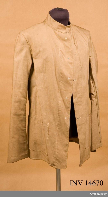 """Grupp C I. Vapenrock av ljust khakifärgat bomullstyg, enradig, 72 cm lång. Två sidofickor utan lock; påsydda. Foder saknas; på tygets baksida finns en pappersetikett med påskriften: """"Royal army clothing factory. Gutters No 9. Trimmers No 1. Reg. No 878.  Maj"""" (sic) """"1920. Size 9. Heigh 5/11 6/0. Breast 38 43. Waist 33 85. Fk. overall. Drab.""""."""