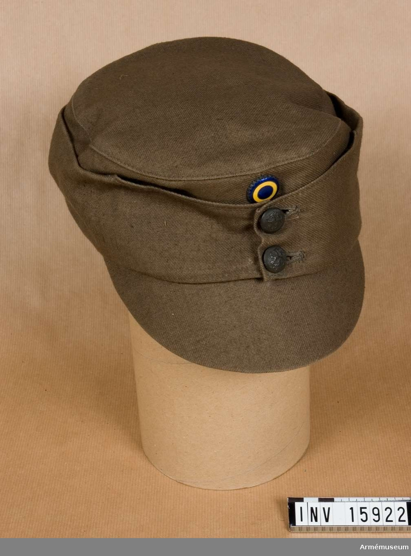 """Grupp C I. Fältmössa för sommarbruk, Svenska Brigaden, 1918, Finland. Buren av general E. Linder. Sommarmössa av bomullstyg, khakifärg, försedd med nedviktbara bräm av samma tyg, framtill två knappar (mindre modell) vapenprydda. Framtill på mössan finns: liten skärm och ovanpå kokard rund gröngul emaljerad, diameter 2 cm. Mössan har foder av grått tyg; på fodret finns fastsydd en lapp på vilken det står: """"Skoha"""" (namn på skyddskårens egen firma, som sålde allt vad en skyddskårist behövde), ovanpå namnet skyddskårens emblem med bokstav """"S"""" (första bokstaven från ordet """"skyddskår"""")."""