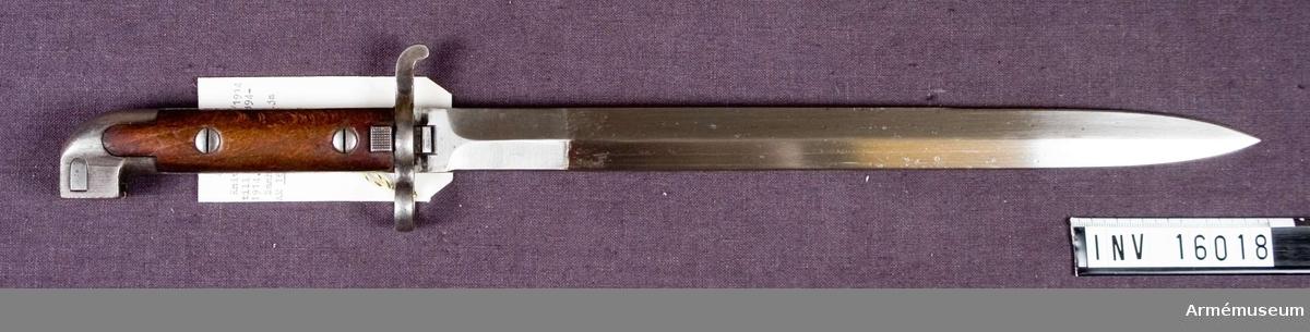 Hel längd 460 mm. Klingans längd 332 mm. Klingans bredd vid fästet 25 mm. Pipringens innerdiameter 15,5 mm.  Grepplattorna av trä fastsatta med skruvar.  Bajonetten försedd med baljlås. Rak tvåeggad klinga. Märkt EJ E AB krona med ankare (Eskilstuna Jernmanufakturaktiebolag).  Samhörande AM 16018 knivbajonett m/1914. AM 16019 balja av stål till bajonett m/1914.