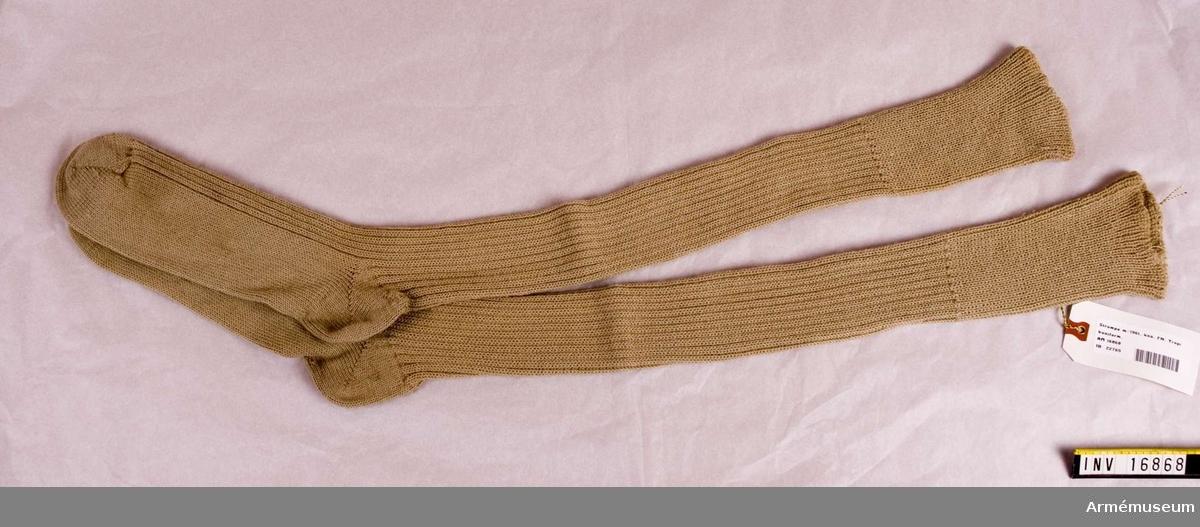 Knästrumpor m/1961 t tropikuniform. Stickade strumpor av beige yllegarn. Två räta, två aviga. Skall vikas ned under knäet.