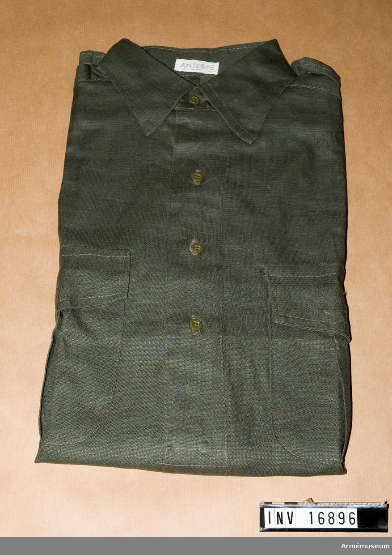 Fältskjorta, indisk modell. En djungelgrön skjorta med ett sprund mitt fram som knäpps med tre knappar. Har fast krage och fasta axelklaffar. Långa ärmar med knäppbara handlinningar. Två bröstfickor med lock, knapp och bälg.