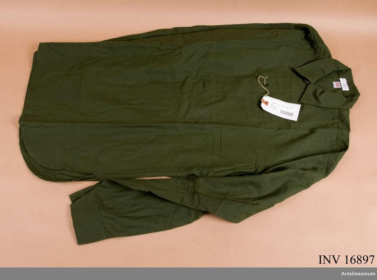 Av olivgrönt tyg med flossad avigsida. avigsida. Den har en 240 mm lång öppning framtill, som knäpps med två knappar. Mjukt nervikt krage, förstärkning upptill på ryggens insida och långa ärmar med knäppbara ärmlinningar. Knapparna är av plast.Ingår i grundutrustning för fältbruk i alla försvarsgrenar i uniformssystem m/1958 och 1959.