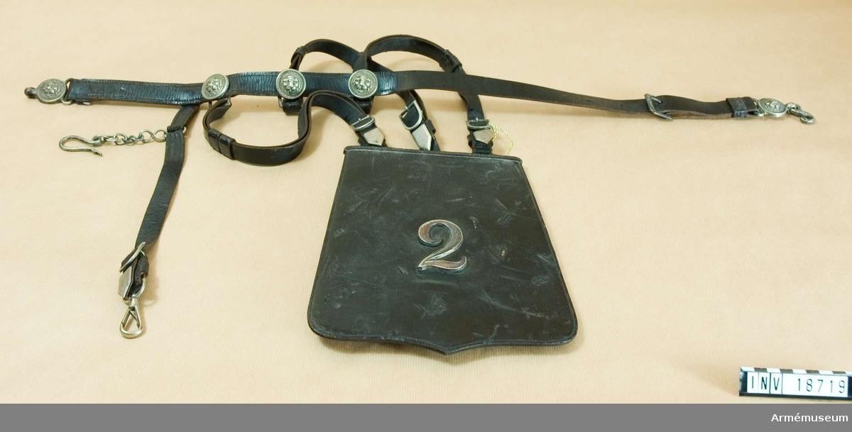 """Grupp C I. Sabeltaska med koppel. Uniform m/1866 för officer, premiärlöjtnant, vid 1., 2. eller 4. Husarreg:a, Blå kavalleriet, Holland. Består av taska (fodral), lock, livbälte och bärremmar. Taska och alla remmar är av svart lackerat läder. Taskan har innerficka med lock, som stänges med en läderknapp. Lock av tjockt läder med fastsatt regementsnummer """"2"""" av vitmetall =Andra husareg:t. Livbälte, b:25 mm, med söljor och beslag (lejonhuvud) av vitmetall, med sabelrem, försedd med karbinhake och kätting med hake för att koppla sabeln. Vid livbältet äro fästade tre bärremmar för taskan, vilka har spännen och beslag av vit- metall. /Enl kapten W Granberg 1954."""
