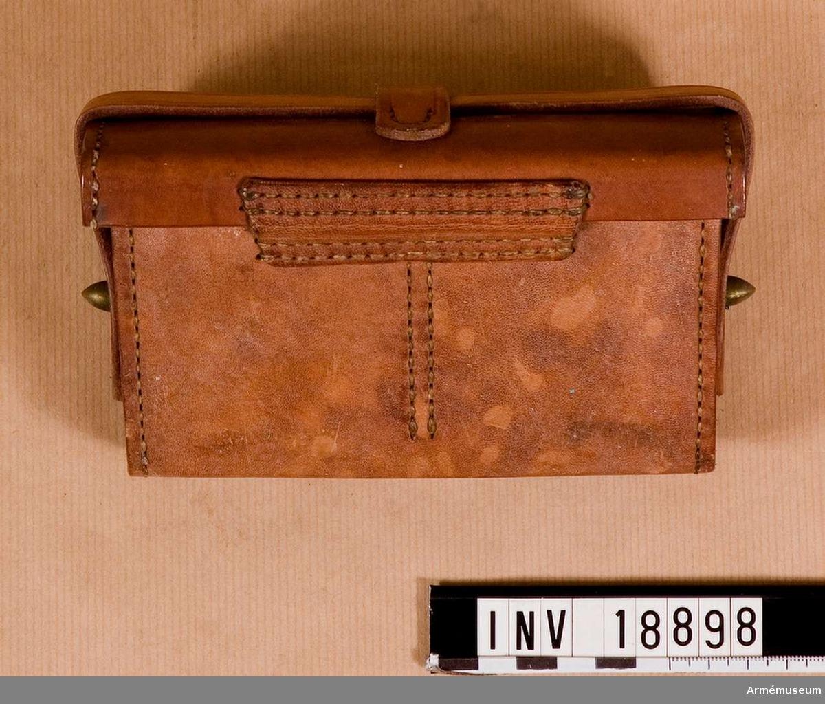 """Grupp C II. Av brunt läder. Består av: Lock som stängs med rem och två knapphål på ändarna. På lockets undersida finnes intryckta japanska stämplar. Väskan har inuti två avdelningar, för två paket patroner med 15 patroner vardera. På sidorna finns 2 knappar för att stänga med rem. På väskans baksida är 2 öglor för livrem fastsydda. LITT  Die Japanische Armée im Jahre 1910. Von ritter v. Ursyn-Pruszyniski. Wien, Teschen, Leipzig 1910. Sida 12 C. Ausrüstung. Infanterie. På livremmen finns 3 patronväskor: 2 på framsidan och en på baksidan. Den 3e väskan bäres på bäres på baksidan och innehåller 60 patroner. Bilaga 7: Infanteriet från baksidan med likadan  patronväska. """"Infanterist in Marschadjustierung""""Enl W Granberg."""