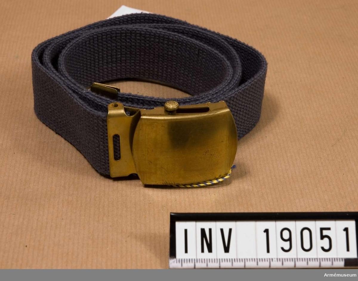 Byxbälte m/1960. Livrem av textilrem med spänne, obehandlat, och ändbeslag i obehandlad  mässing. Avsett för uniform m/1960 och KA m/1960 men utgör också version av byxbälte i alla försvarsgrenar.