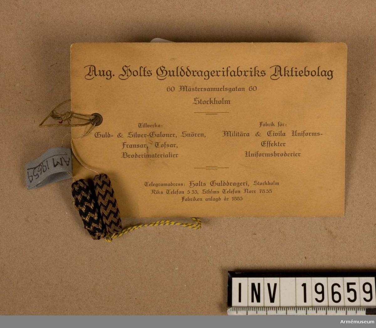 """Knapparna är flätade på olika sätt. Den ena har ett zig-zag mönster i guld, den andra har ett flätmönster i guld och svart. Båda knapparna är svarta och guldfärgade. På den tillhörande etiketten fr. Aug. Holts Gulddragerifabriks Aktiebolag, står det, handskrivet: """"Knappar nålade."""" August Holts Gulddragerifabriks Aktiebolag grundades 1885. 1906 sattes företaget i likvidation, men nyregistererades 1909. Till 1983 försåg företaget framförallt militären med tofsar och band vävda av guldtråd i någon form. Men alltfler av militärens order lades utomlands, i Asien, där produktionen var billigare. Aug. Holts Gulddragerifabriks AB fick svårt att klara konkurrensen, trots att deras varor höll högre kvalité än de importerade. När firman upphörde 1983 fick Nordiska museet en stor del av lagret. De kontaktade Armémuseum. Irma Wallenborg och Gunvor Klingberg fick välja ut material med militär anknytning. Men huvuddelen av samlingen finns dock fortfarande i Nordiska museet."""