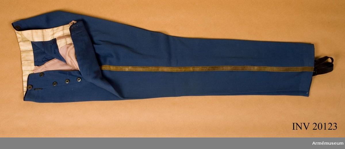 """Grupp C I. Ur uniform för major vid Gendarmeriet, Persien.  Består av vapenrock, långbyxor, ridbyxor, kappa, sabelkoppel, mössa, kordong, ägiljett. Buren av K Killander (1886-1951) under tjänstgöring i Persiska armén 1912-14. Av kläde, ljusblått, med två sidofickor på framsidan. Foder av randigt bomullstyg. Längs yttersömmarna 2 breda guldgaloner. Hällor av gummiband med 2 benknappar. På knapparna finns tillverkarens stämpel: """"G.A.Lundkvist, Stockholm"""" =skrädderifirma."""