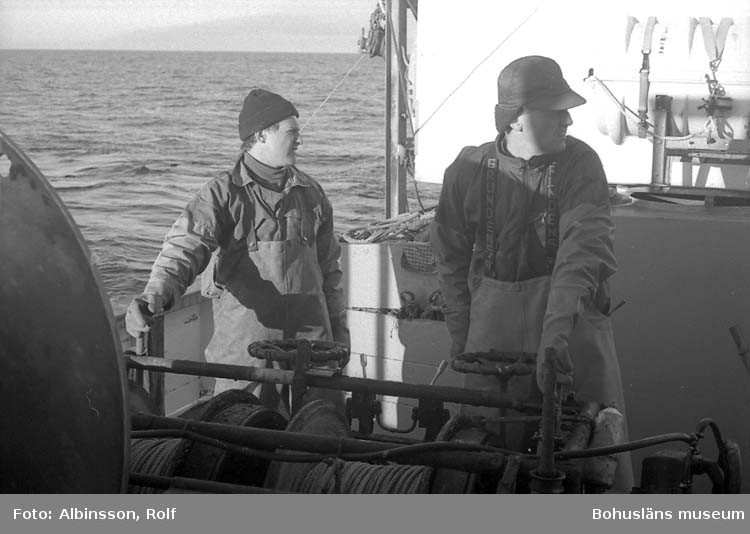 """Enligt fotografens noteringar: """"Klockan är 7.30, dags att ta in wiren, det sköter Harald Hansson och Bengt Persson.""""  Fototid: 1996-03-07."""