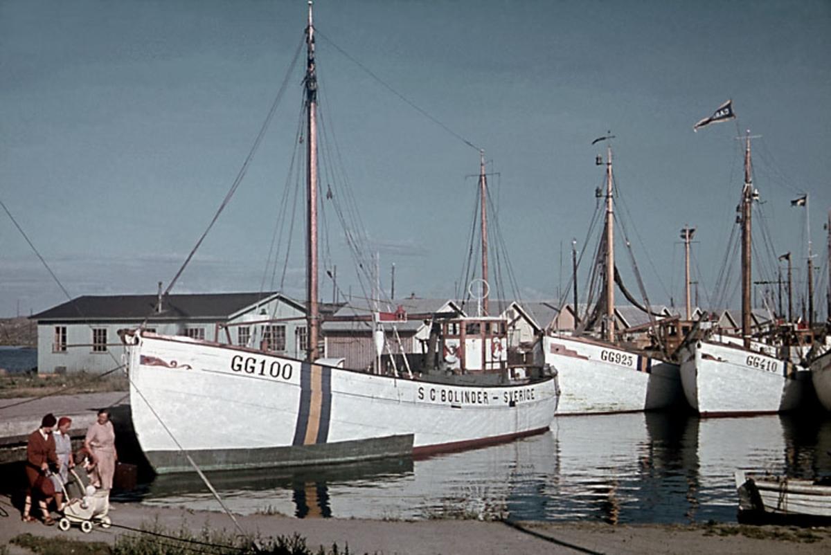 """Enligt noteringar: 70 st. ramade dia. + 5 st. burkar med oramade dia. Båtar, Varv, Hav. Film nr. 129 Hönö, Klova hamn. Gamla cyckelverkstaden t.h.  GG 100 """"S.G. Bolinder"""" Hönö (skeppare Gösta Hansson ej på bild) GG 925 """"Beltana"""" Hönö (minsprängd den 13 jan. 1945; skeppare Albert Lisborg ej på bild) GG 410 """"Carmel"""" Fotö (skeppare Osborne Krook ej på bild)"""