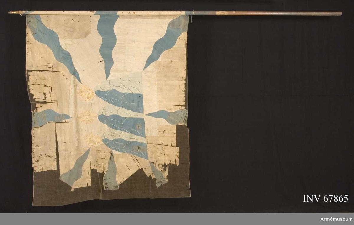 Duk: Tillverkad av vit taft. Duken fäst med svartkantat vitt sidenband och förgyllda spikar.  Dekor:  Insydda från hörnen och mitt på blå flammor, kantade med blått silke. I mitten Västmanlands vapen, 3 eldsprutande berg i mörkare och ljusare blå taft med konturer i blått silke samt lågor i röd taft (mycket blekt) och gult silke.   Stång av furu, något blåmålad. Holk av mässing.  Märkt:  På stången krigskollegii lapp No 2 (Lrk)