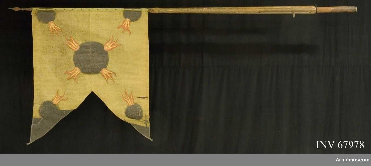 Duk: Tillverkad av enkel grön sidendamast, sydd av två horisontella våder.  Mönsterrapport, kraftigt stiliserat blommönster.  Dekor: Målad lika på båda sidor, i mitten en stor fyrkula i silver, övertränsad med svart och utsändande fyra lågor, i hörnen mindre kulor med inåtriktade låga. Fäst vid stången med rosformiga tennlikor på ett ljusgrönt sidenband.   Stång av grönmålad furu. Kanellerad ovanför greppet, slät nedanför. Löpande bärring. Holk och spets av järn. Spetsen går ned på stången, fäst med spikar med kupiga, stora huvuden.