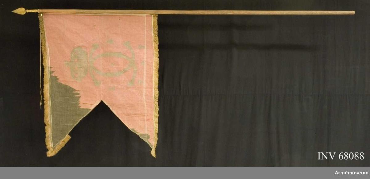 """Duk: Tillverkad av enkel röd sidendamast sydd av två horisontella våder. Fäst vid stången sekundärt med små mässingsstift.  Dekor: Målad lika på båda sidor, namnchiffer dubbel C under sluten krona. På ömse sidor om chiffret """"1 6"""" samt under """"7 9"""".   Stång: Tillverkad av målad furu, rund holk.   Spets: Tillverkad av förgylld mässing, lansettformad.   Frans: Enkel av gult silke och silver.  Banderoll: Tillverkad av flätat gult silke (samma färg som fransen)."""
