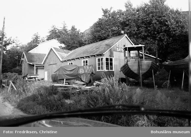 """Motivbeskrivning: """"Båtbyggare Karl Olsson, Ellös. Båtbyggarverkstaden. Rikt: NÖ. 1979."""""""