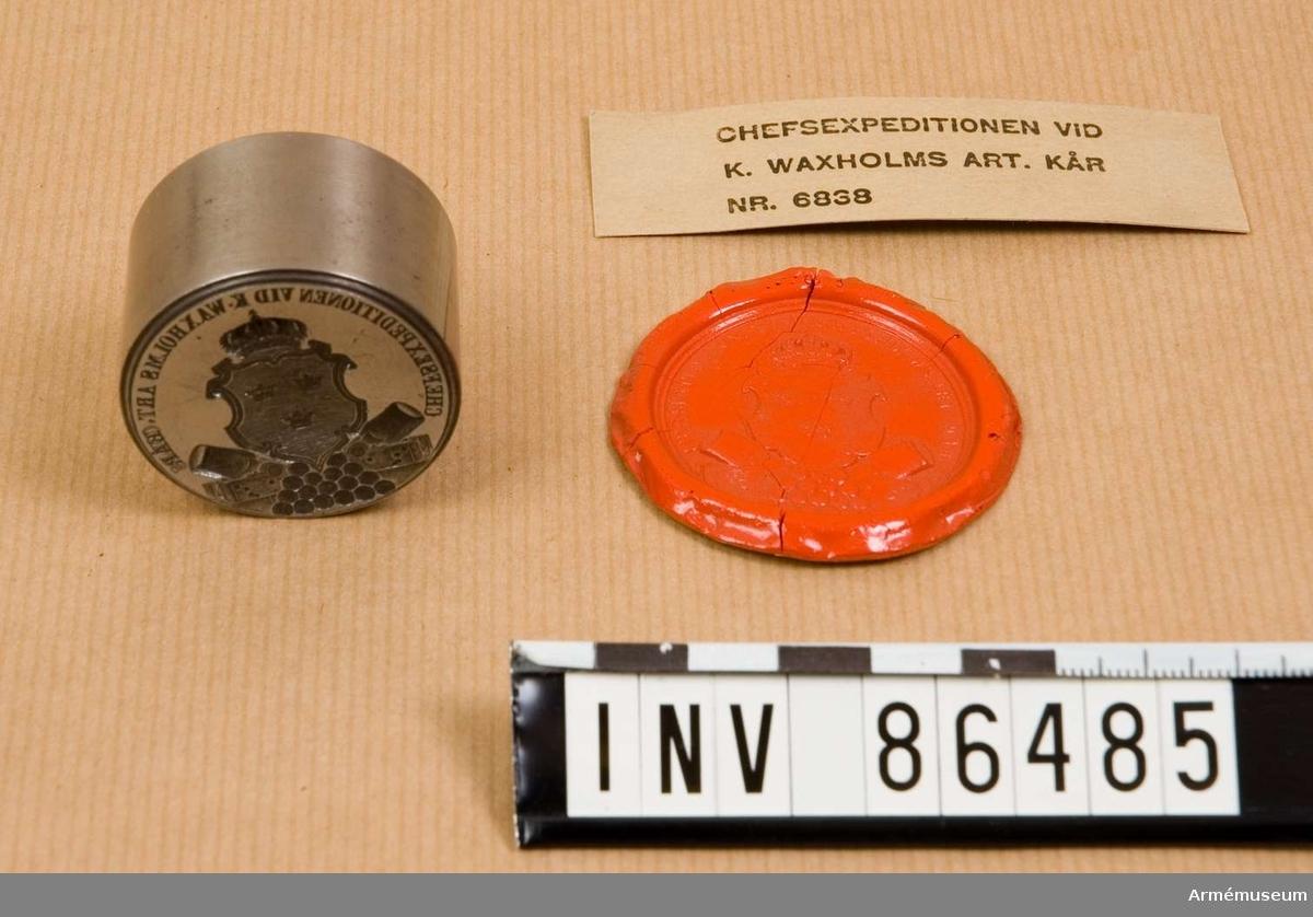 Grupp M V. En räfflad sköld med Sveriges tre kronor, omgiven av en ram i rococostil. Ovanpå skölden en kunglig krona. På sidorna om sköldens nedersta spets: två utåtvända mörsare på lavetter. Nederst en pyramid av kanonkulor. Med avtryck i röd lack.