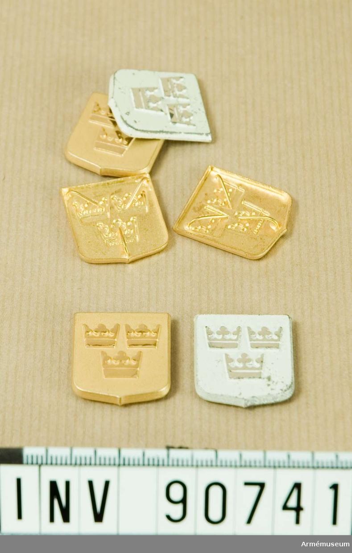Låda innehållande fyra guldfärgade och två vitmålade märken föreställande tre kronor.