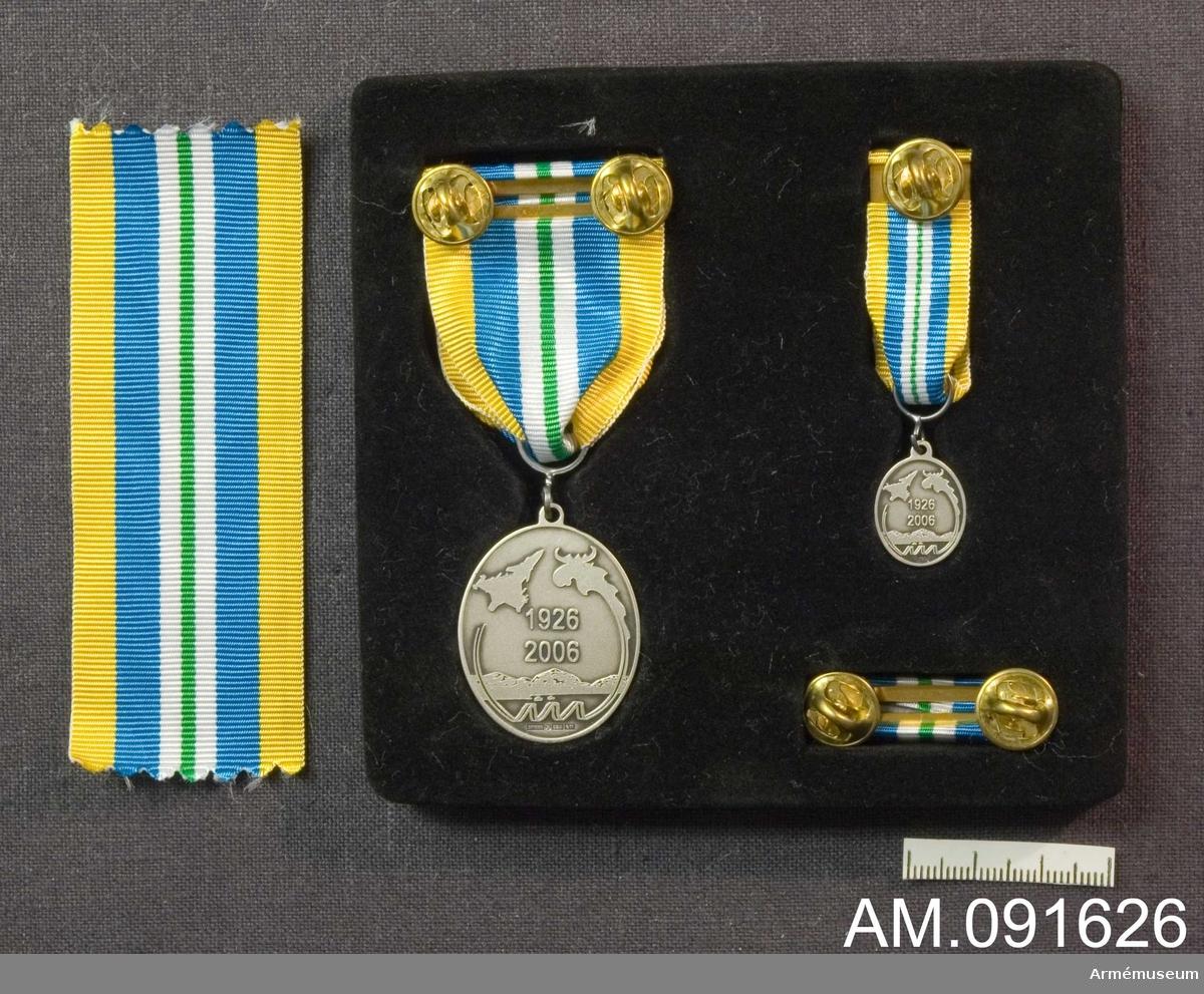 Etui innehållande Medalj, minimedalj samt släpspänne.  Märkt på framsidan med Jämtlands flygflottilj vapen. Årtalen finns på baksidan. Band i gult med ett grönt streck på mitten åtföljt på båda sidor av först en vit rand därefter en bredare blå rand.
