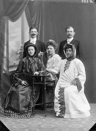 """Enligt senare noteringar: """"Ateljéfoto av två män, tre kvinnor, samtliga finklädda, två av kvinnorna i fantasidräkt."""""""
