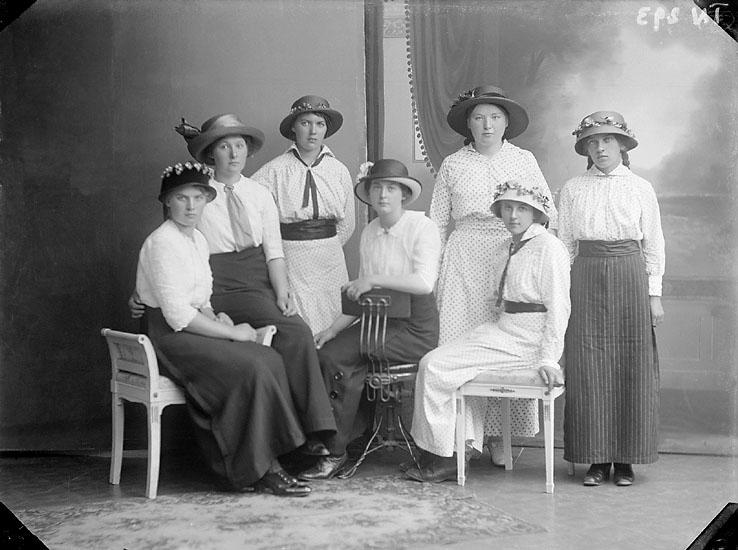 """Enligt senare noteringar: """"Ateljéfoto, sju unga damer med hattar, klädda i kjol och blus eller klänning."""""""