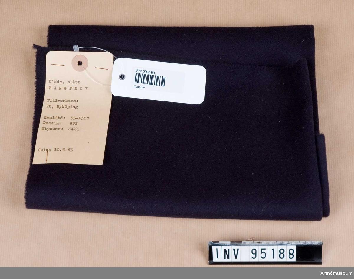 """Text på etiketten: """"Kläde, blått. FÄRGPROV Tillverkare: YK, Nyköping. Kvalité: 55-6307, Dessin: 532, Stycknr: 8461. Solna 10.6-65"""""""