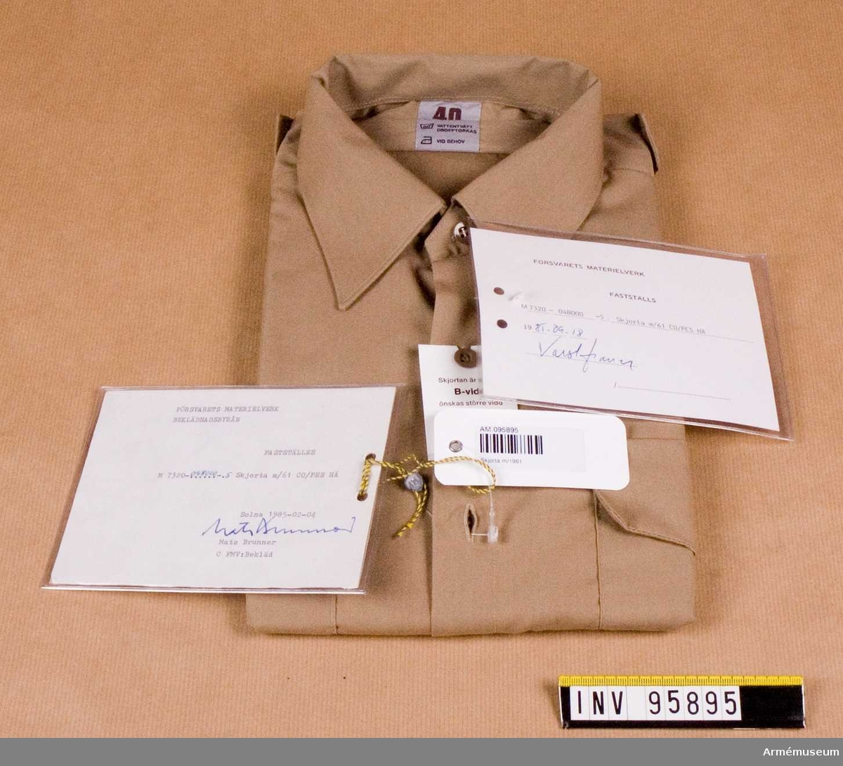"""Skjorta med hel, fast krage och ok av dubbelt tyg och kort ärm (tidigare benämnd halvlång). Skjortan har bröstfickor med knäppbart lock. Fasta axelklaffar, bredd 42-45 mm utan axelklaffshylsor. Skjortan är avsedd för uniform m/61 (tropikuniformen) och flottans långresedräkt. Två vidhängande etiketter. Text på den ena: """"Försvarets materielverk Fastställs M 7320-048000-5, Skjorta m/61 CO/PES HÄ, 1985-09-05  (oläslig underskrift)"""". Den andra etiketten är från beklädnadsbyrån och har likalydande text. Underskriven 1985-02-04 av Mats Brunner. På baksidan stämpel från arméstabens FN-avdelning och underskrift av Major Martin Waenseth."""