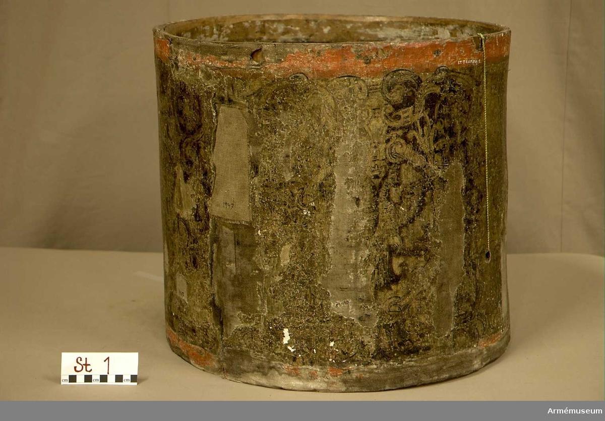 Cylindertrumma av: trä. Cylindern är klädd med en lim-& kritgrunderad duk som är dekorerad. Ytan är säkrad på något vis vid konserveringstillfället år 1947. Grunderingen är krackelerad med ett stort bortfall som på sina ställen frilägger duken helt. Delar av träcylindern är utbytta och märkta med 1947. Likaså har man gjort med utsidan, där tygbitar är fastlimmade, även dessa är märkta med 1947.                      Membran : saknas. Veckelgjordar: saknas. Spännlina: saknas. Spännringar: saknas. Sejarhållare: saknas.  Utsmyckning: förgylld botten med  fyra medaljonger, dubbelörnar och slingor i barock stil. Konturerna är ristad i grunderingen. Märkning: finns.