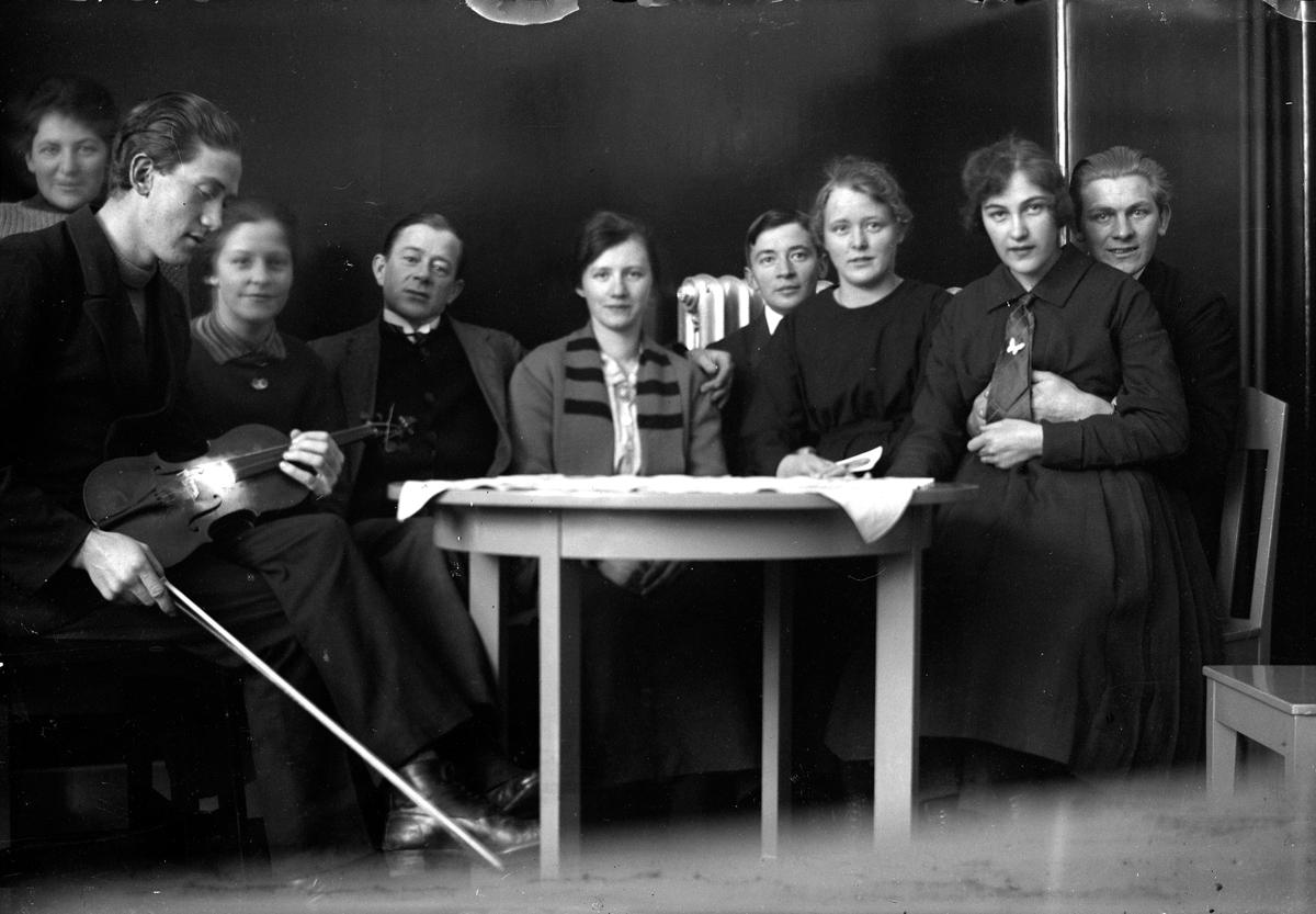 Fem kvinnor och två män, varav en håller en fiol, sitter vid ett bord.   Lungkliniken i Eksjö.