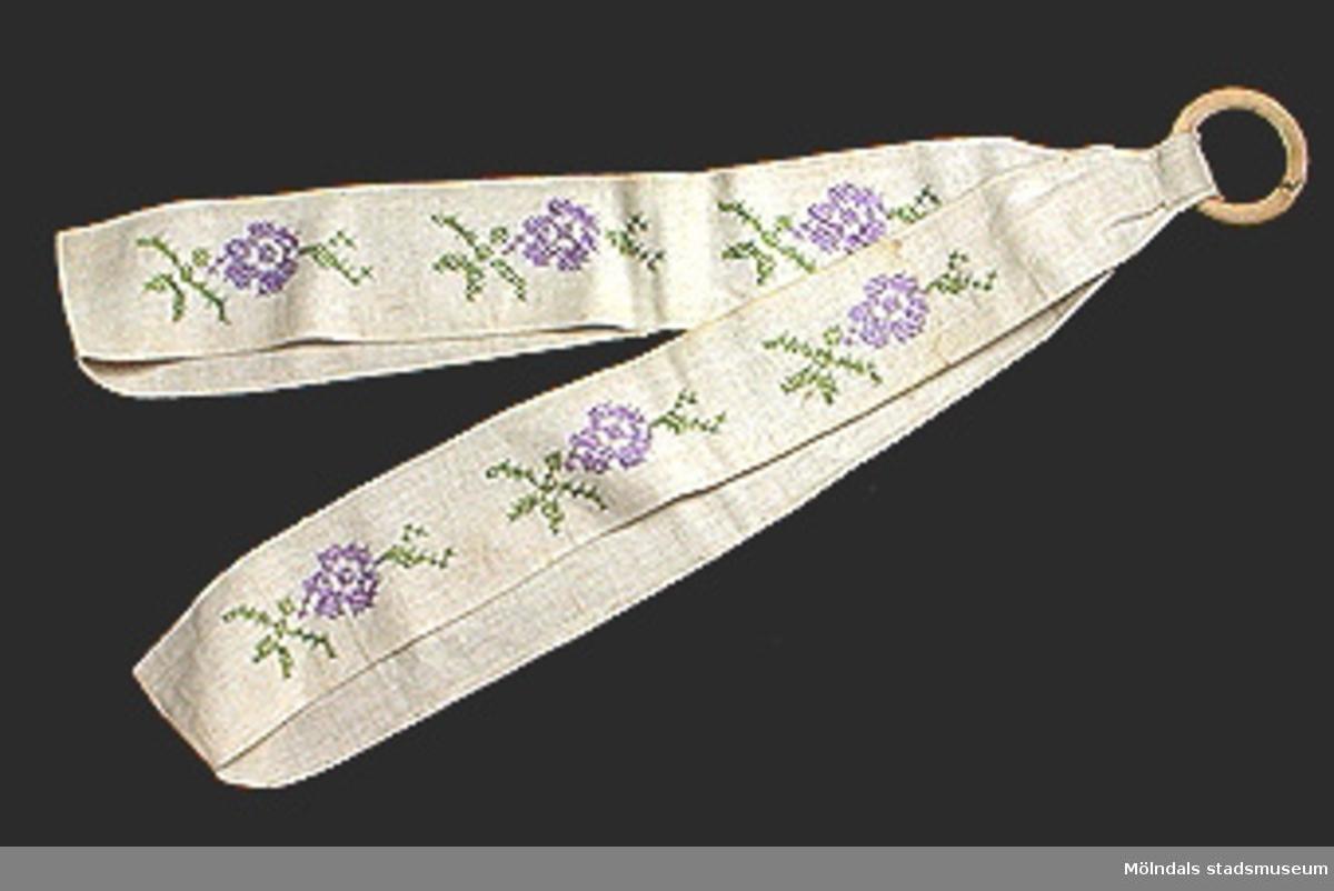 Två brickband i naturfärgat linne. Sammanhållna i träring för upphängning. Maskinsytt. Stiliserade blommor broderade i korsstygn i grönt och lila. Moulinégarn. Fläckigt.